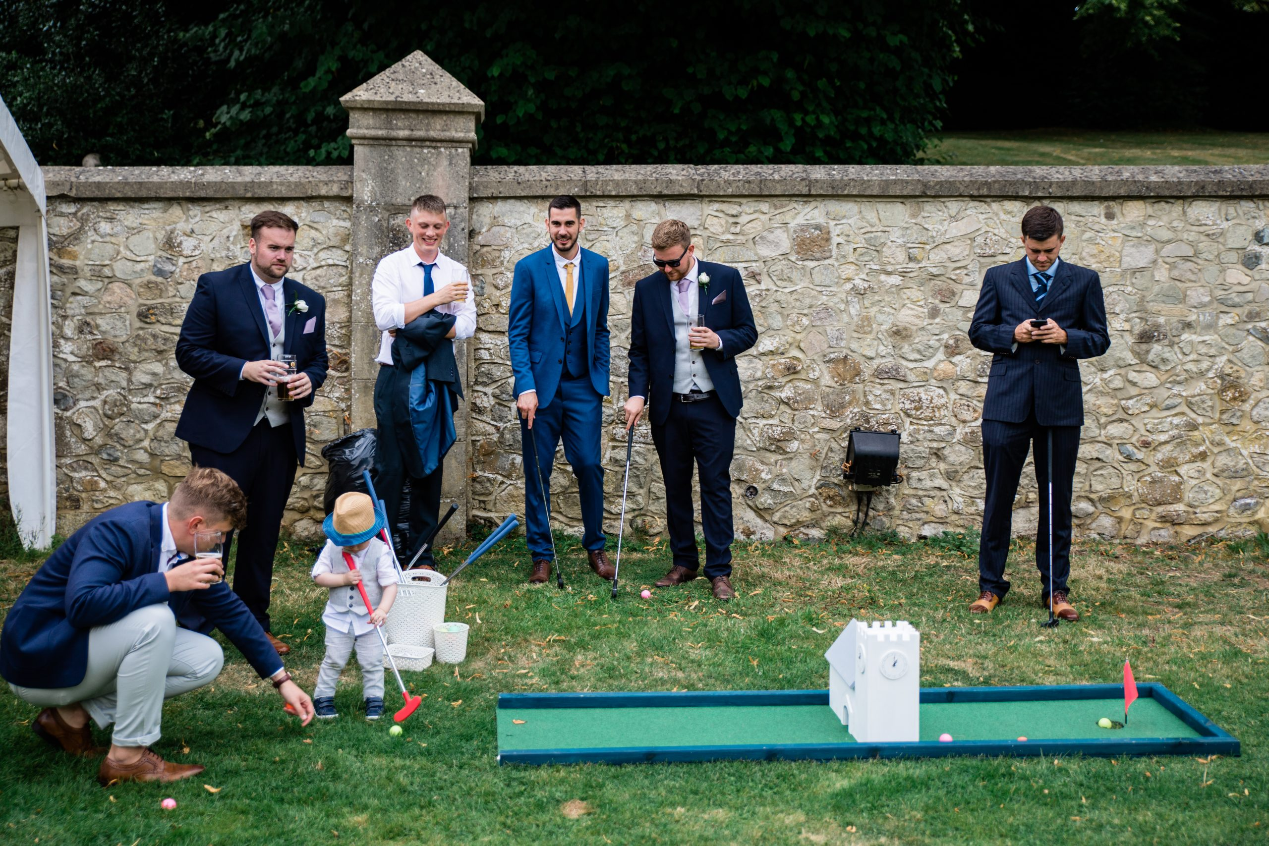 groomsmen and child playing mini golf